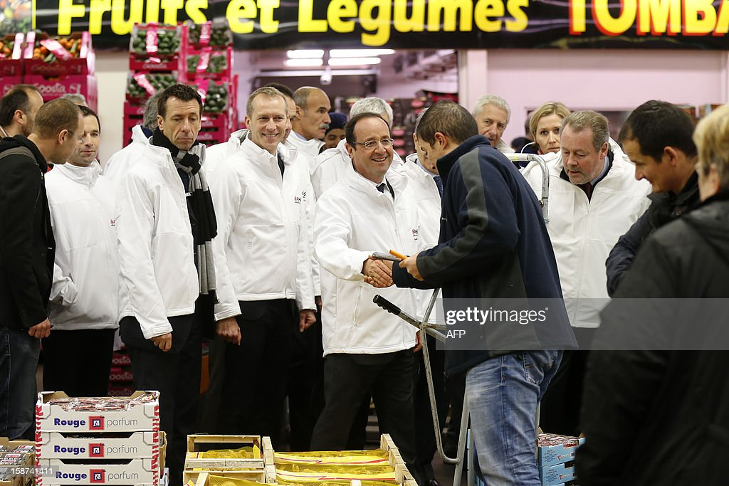 French President Francois Hollande (C) shakes hands with workers as he visits the Rungis wholesale market in Rungis, near Paris on December 27, 2012.