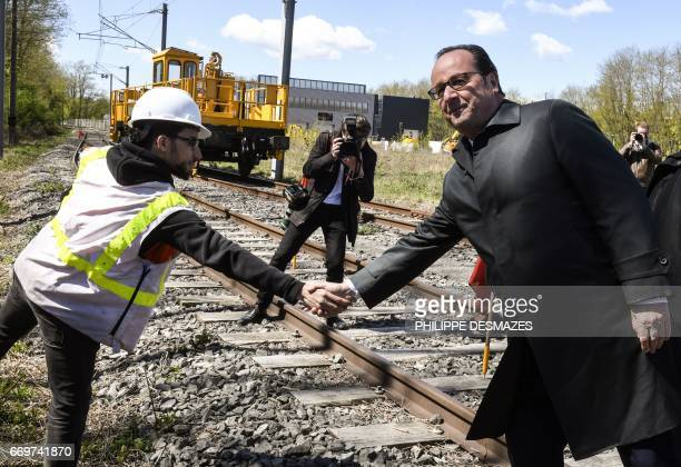 French President Francois Hollande shakes with a worker during a visit to the Mecateamcluster maintenance and construction platform in SaintVallier...