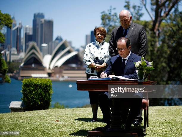 French President Francois Hollande signs a guestbook in front of the Sydney Opera House before an official lunch with Australia's GovernorGeneral...