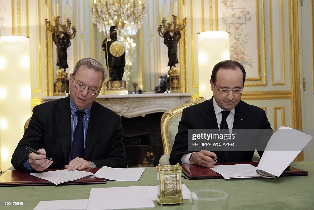 French President Francois Hollande (R) signs an agreement with Google Executive Chairman Eric Schmidt at the Elysee Presidential Palace on February 1, 2013 in Paris.