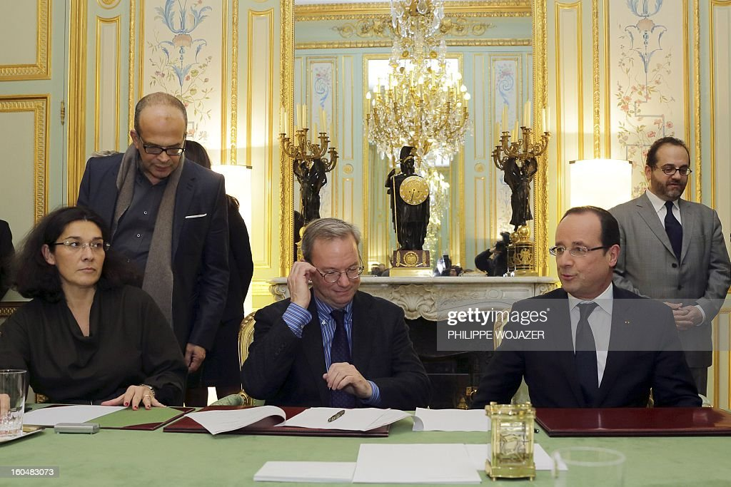 French President Francois Hollande (2ndR) signs an agreement with Google Executive Chairman Eric Schmidt (C), flanked by negociator Marc Schwartz (R), press association President Nathalie Collin (L) and Media advisor David Kessler (2ndL) at the Elysee Presidential Palace on February 1, 2013 in Paris.