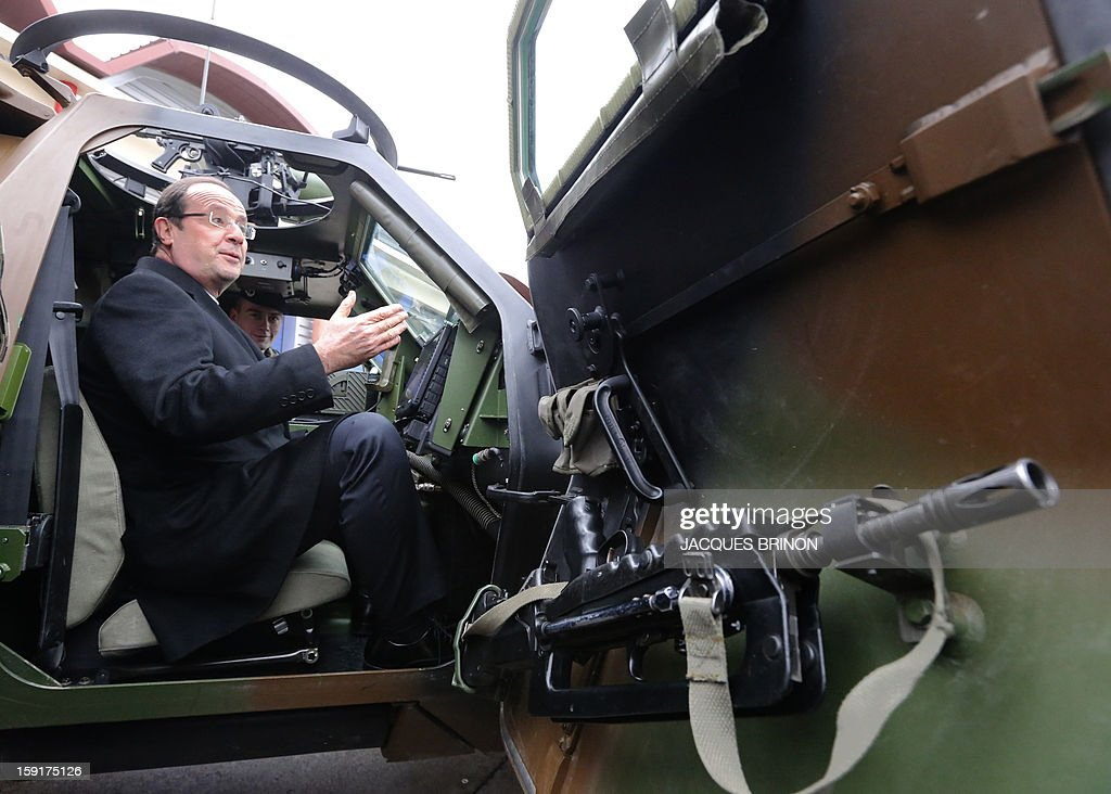 French President Francois Hollande sits in an armored vehicule of the 12th cuirassiers regiment at the military base of Olivet, central France, as part of a visit to present his New Year's wishes to the French armed forces, on January 9, 2013.