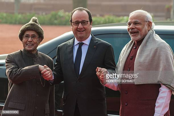 French President Francois Hollande smiles as he holds the hands of Indian President Pranab Mukherjee and Indian Prime Minister Narendra Modi as they...
