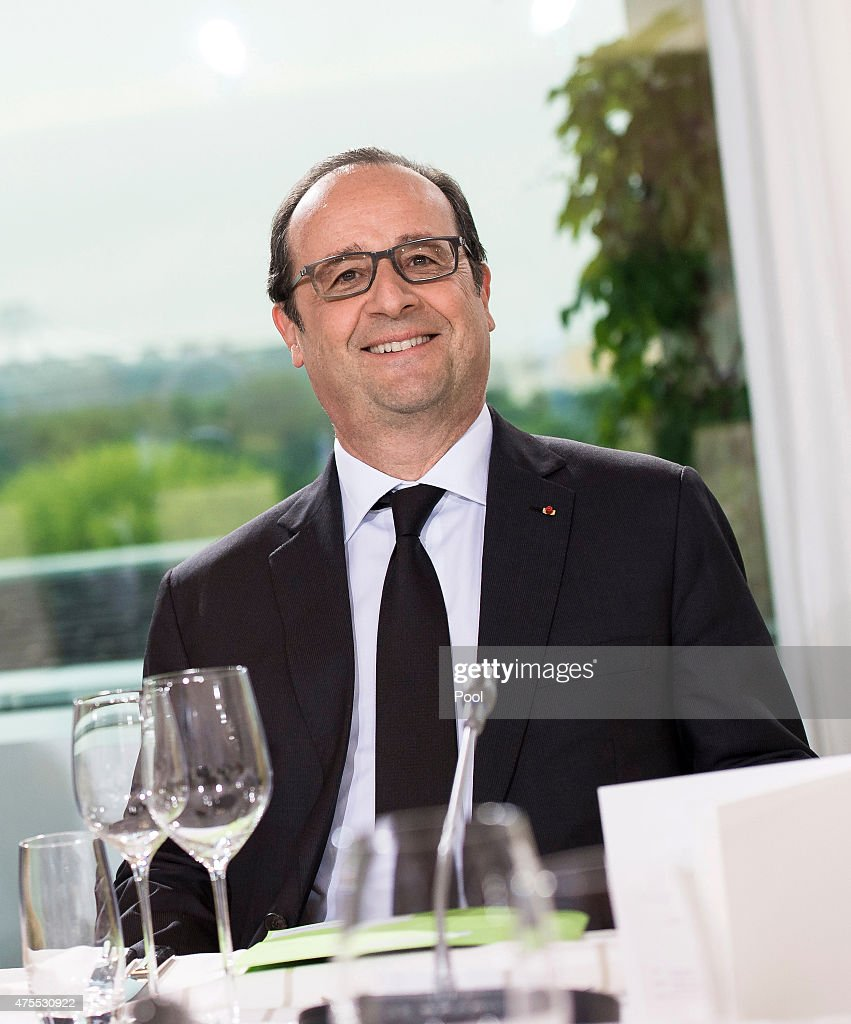 French President Francois Hollande smiles as he sits down for dinner at the Chancellery on June 1, 2015 in Berlin, Germany. The three leaders are meeting to discuss the ongoing Greek financial crisis that has become more urgent as a possible bankruptcy by Greece is looming.