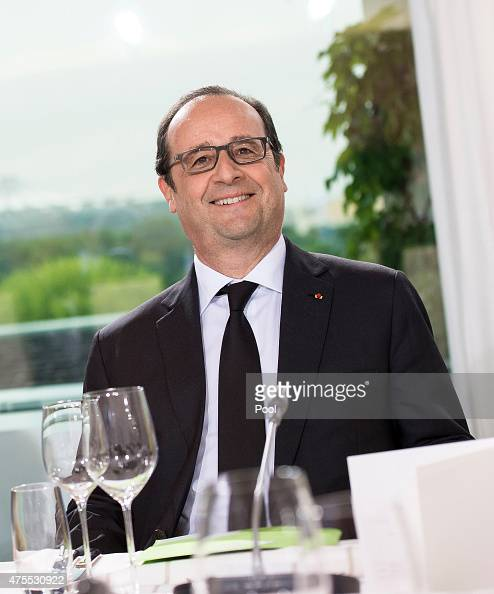 French President Francois Hollande smiles as he sits down for dinner at the Chancellery on June 1 2015 in Berlin Germany The three leaders are...