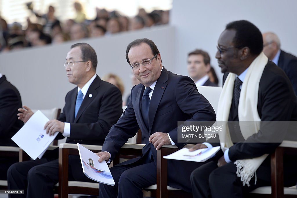 French President Francois Hollande (C) smiles next to Malian President Dioncounda Traore (R) and United Nations General Secretary Ban Ki-Moon during the Bastille Day parade at the Place de la Concorde, on July 14, 2013 in Paris.