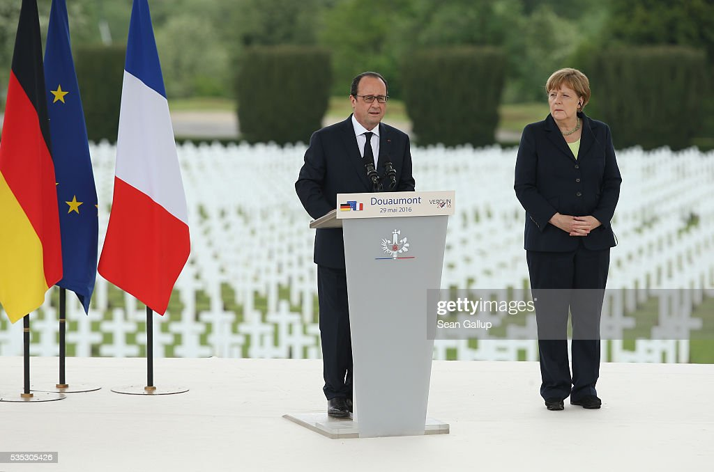 French President Francois Hollande speaks as German Chancellor Angela Merkel looks on during ceremonies to commemorate the 100th anniversary of the World War I Battle of Verdun at the Douaumont cemetery on May 29, 2016 near Verdun, France. The 1916, 10-month battle pitted the French and German armies against one another in a grueling campaign of trench warfare and artillery bombardments that killed a total of approximately 300,000 soldiers. The events today coincide with the 50th anniversary of commemorations held at Verdun by then French President Charles de Gaulle and German Chancellor Konrad Adenauer that paved the way for a new era of peaceful, post-war Franco-German relations.