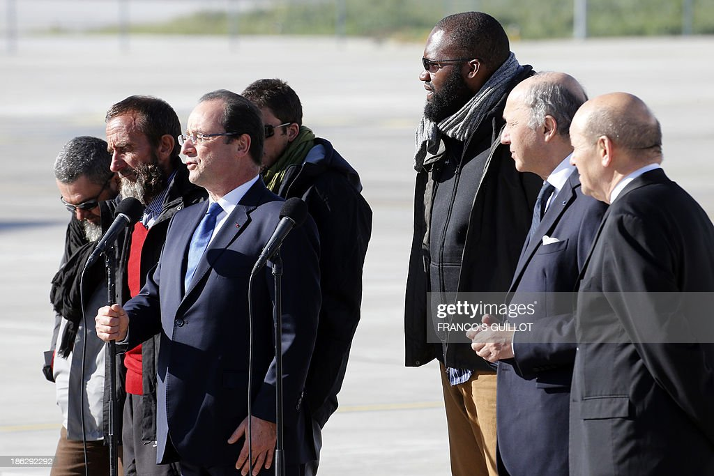French President Francois Hollande (3rdL), speaks as he welcomes (FromL) former French hostages Marc Feret, Daniel Larribe, Pierre Legrand, and Thierry Dol, next to French Defence Minister Jean-Yves Le Drian (R) and French Foreign Affairs minister Laurent Fabius (2ndR), at the military airport of Villacoublay outside Paris, on October 30, 2013. Four French hostages who were kidnapped by Al-Qaeda in the Islamic Maghreb in northern Niger in 2010 have been released on October 29. Frenchmen Thierry Dol, Daniel Larribe, Pierre Legrand and Marc Feret were working for French nuclear giant Areva when they were kidnapped on September 16, 2010, from a uranium compound in Arlit, north-central Niger.