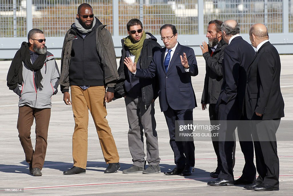 French President Francois Hollande (C), speaks as he welcomes (FromL) former French hostages Marc Feret, Thierry Dol, Pierre Legrand and Daniel Larribe, next to French Foreign Affairs minister Laurent Fabius andh Defence Minister Jean-Yves Le Drian, at the military airport of Villacoublay outside Paris, on October 30, 2013. Four French hostages who were kidnapped by Al-Qaeda in the Islamic Maghreb in northern Niger in 2010 have been released on October 29. Frenchmen Thierry Dol, Daniel Larribe, Pierre Legrand and Marc Feret were working for French nuclear giant Areva when they were kidnapped on September 16, 2010, from a uranium compound in Arlit, north-central Niger.