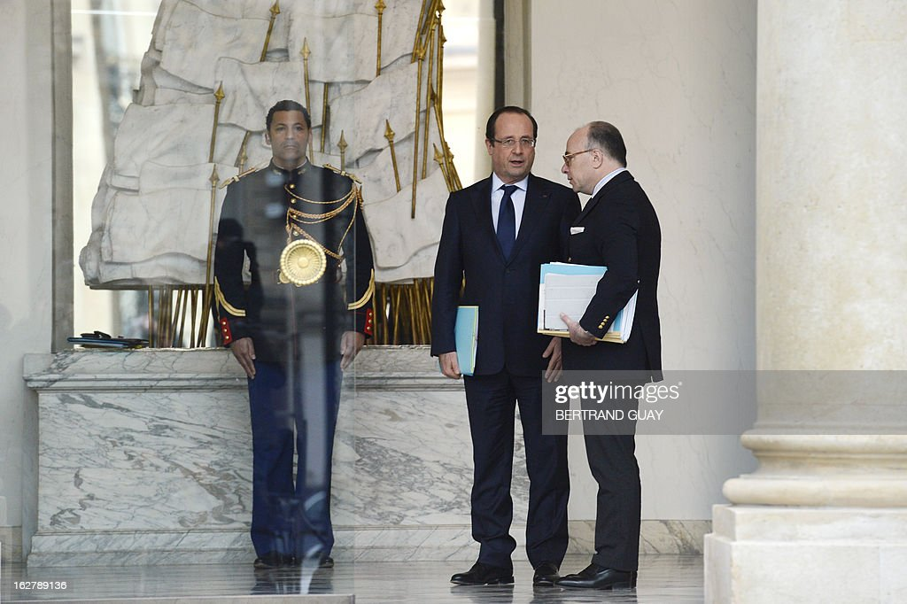 French President Francois Hollande (C) speaks to French Junior Minister for European Affairs Bernard Cazeneuve on February 27, 2013 following the weekly cabinet meeting at the Elysee Presidential Palace in Paris. AFP PHOTO BERTRAND GUAY