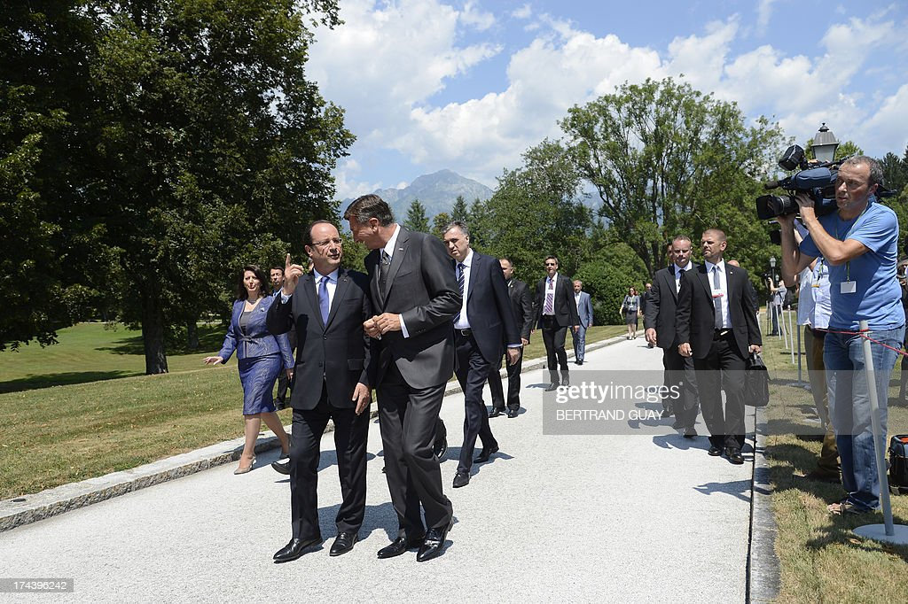 French President Francois Hollande (L) speaks to his Slovenian counterpart Borut Pahor after posing for a group photo during The Leaders' Meeting of Brdo Process in Brdo Pri Kanju on July 25, 2013. The presidents of eight western Balkans countries along with French president Francois Hollande met in Slovenia at an unprecedented summit aimed at promoting cooperation and further EU's enlargement in the region. The summit was organized by the presidents of the only two former Yugoslav states that joined the EU, Slovenia's Borut Pahor and Croatia's Ivo Josipovic, and backed by the French president underlining the need for reforms for all Balkans states that would like to join the EU.