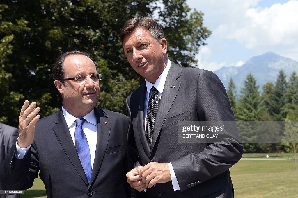 French President Francois Hollande (L) speaks to his Slovenian counterpart Borut Pahor after posing for a group photo during The Leaders' Meeting of Brdo Process in Brdo Pri Kanju on July 25, 2013. The presidents of eight western Balkans countries along with French president Francois Hollande met in Slovenia at an unprecedented summit aimed at promoting cooperation and further EU's enlargement in the region. The summit was organized by the presidents of the only two former Yugoslav states that joined the EU, Slovenia's Borut Pahor and Croatia's Ivo Josipovic, and backed by the French president underlining the need for reforms for all Balkans states that would like to join the EU. AFP PHOTO / BERTRAND GUAY