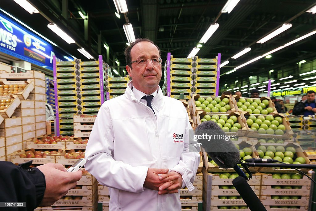 French President Francois Hollande (C) speaks to the journalists as he visits the Rungis wholesale market in Rungis, near Paris on December 27, 2012.