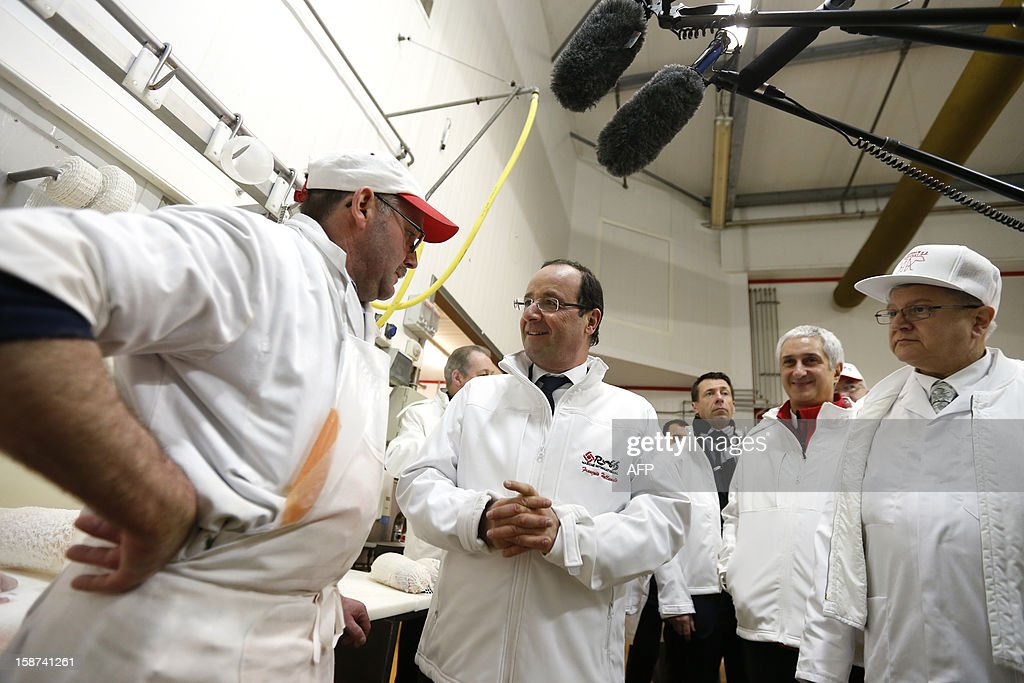 French President Francois Hollande (C) speaks with a butcher as he visits the meat pavilion at the Rungis wholesale market in Rungis, near Paris on December 27, 2012.
