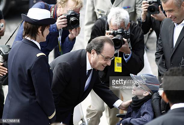 French President Francois Hollande speaks with a child after the annual Bastille Day military parade on July 14 2016 in Paris France France holds...