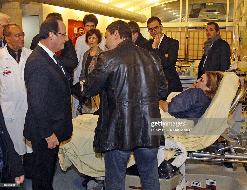 French President Francois Hollande (L) speaks with a patient's husband as he visits the Lariboisiere hospital, on December 31, 2012 in Paris.