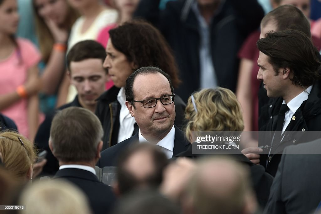 French President Francois Hollande speaks with a woman as he attends a remembrance ceremony to mark the centenary of the battle of Verdun, at the Douaumont Ossuary (Ossuaire de Douaumont), northeastern France, on May 29, 2016. The battle of Verdun, in 1916, was one of the bloodiest episodes of World War I. The offensive which lasted 300 days claimed more than 300,000 lives. / AFP / FREDERICK