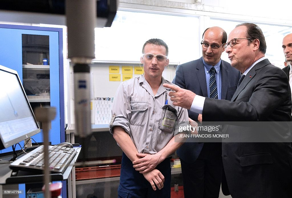 French President Francois Hollande (R) speaks with a worker as he visits the MK Automotive Mecachrome plant on May 4, 2016 in Sable-sur-Sarthe, northwestern France. / AFP / JEAN
