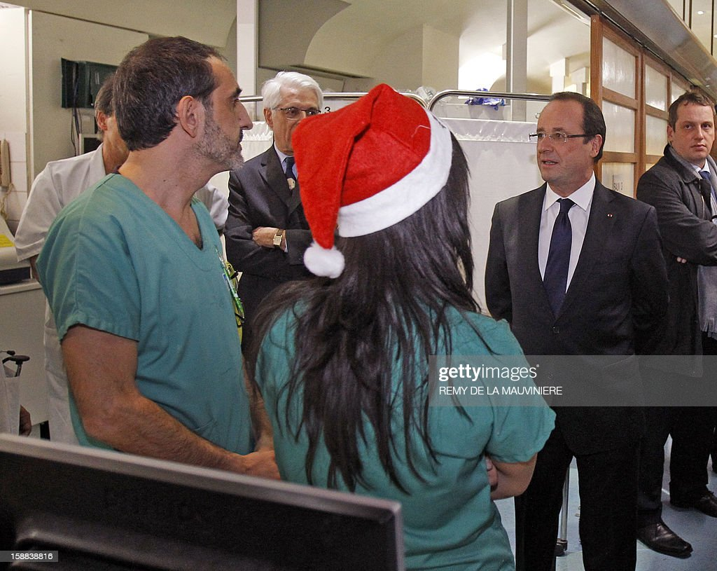 French President Francois Hollande (R) speaks with employees and medics as he visits the Lariboisiere hospital, on December 31, 2012 in Paris.