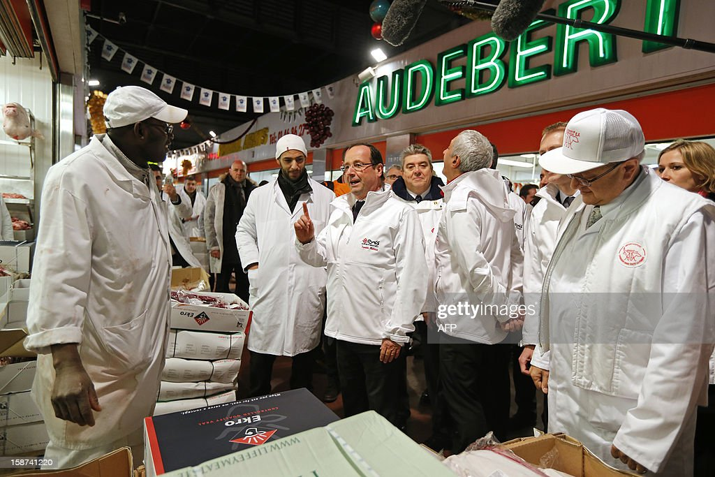 French President Francois Hollande (C) speaks with employees as he visits the Rungis wholesale market in Rungis, near Paris on December 27, 2012.