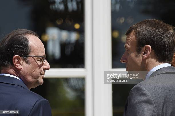 French President Francois Hollande speaks with French Economy and Industry Minister Emmanuel Macron after posing for a family photo following the...