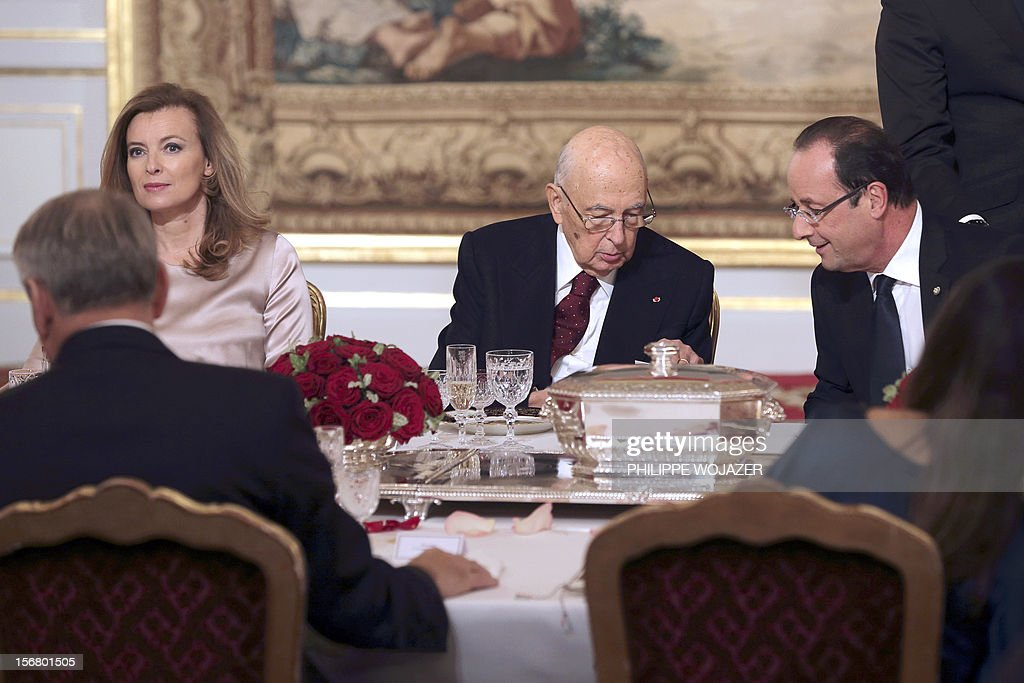 French President Francois Hollande (R) speaks with Italian President Giorgio Napolitano (C) during a state dinner at the Elysee Palace in Paris, November 21, 2012. At left President Hollande's companion Valerie Trierweiler. AFP PHOTO POOL /PHILIPPE WOJAZER