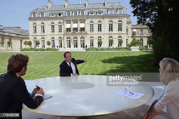 French President Francois Hollande speaks with journalists Laurent Delahousse and Claire Chazal after a television interview in the garden of the...