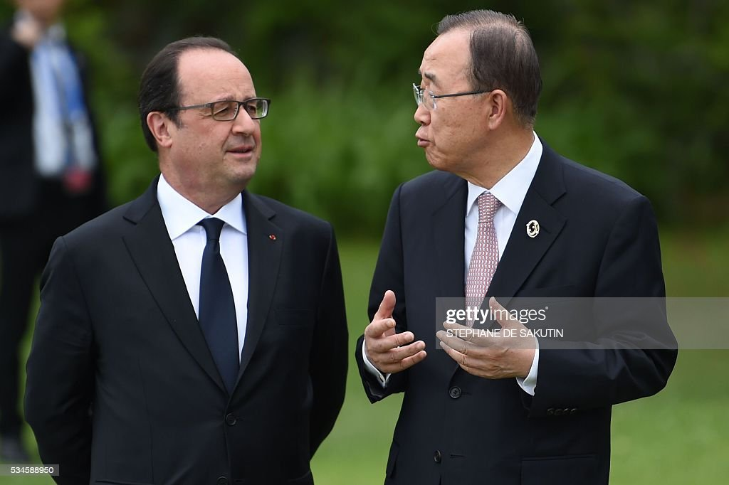 French President Francois Hollande (L) speaks with UN Secretary General Ban Ki-moon as they join other leaders of the Group of Seven (G7) nations as they line up for a family photo with other invited leaders at the G7 Summit in Shima in Mie prefecture on May 27, 2016. A British secession from the European Union in next month's referendum could have disastrous economic consequences, G7 leaders warned on May 27 at the close of the summit in Japan. / AFP / STEPHANE