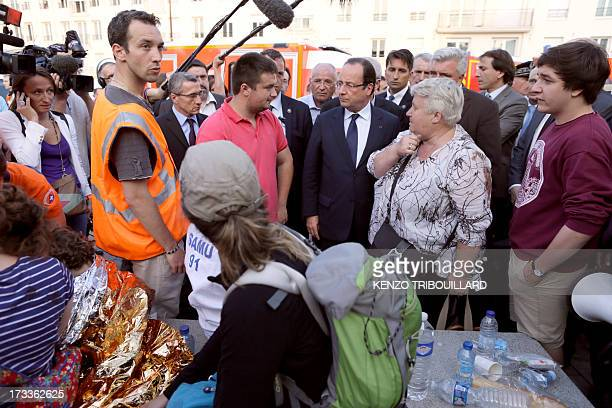French president Francois Hollande speaks with victims and rescue workers on the site of a train accident on July 12 2013 at the railway station of...