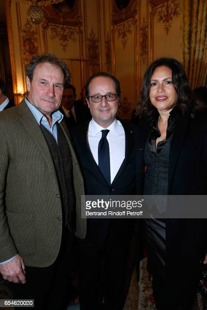 French President Francois Hollande standing between Francis Lombrail with his wife Viktor Lazlo attend Michel Bouquet is elevated to the Rank of...
