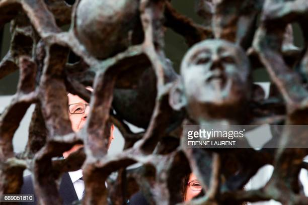 French President Francois Hollande stands behind a sculpture by German born and French artist Haim Kern entitled 'They didn't choose their tomb'...