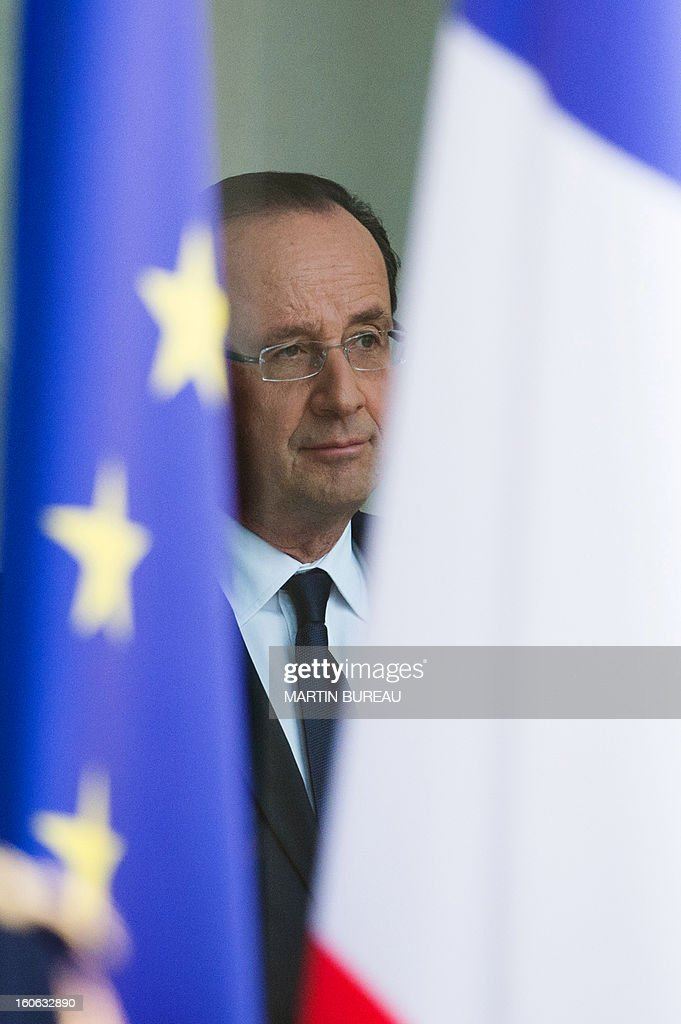 French president Francois Hollande stands between the EU (L) and French flags as he waits for US vice president Joe Biden at the Elysee Palace, on February 4, 2013 in Paris.
