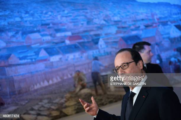 French President Francois Hollande stands in front of a monumental 1900 painting by Gaston Roullet then official painter of the French Navy depicting...