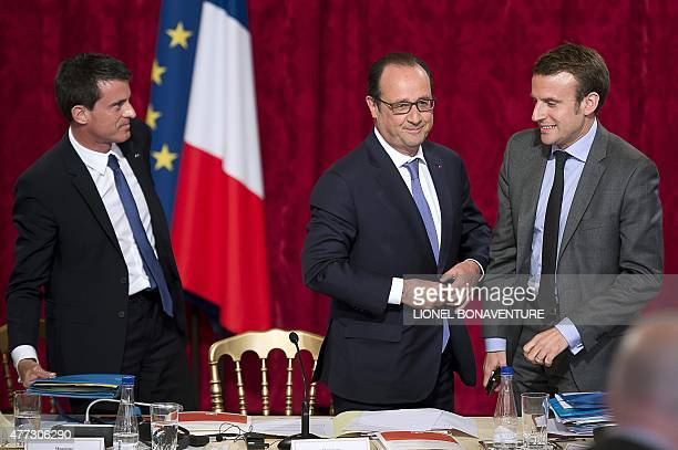 French President Francois Hollande stands next to French Prime Minister Manuel Valls and French Economy and Industry minister Emmanuel Macron during...