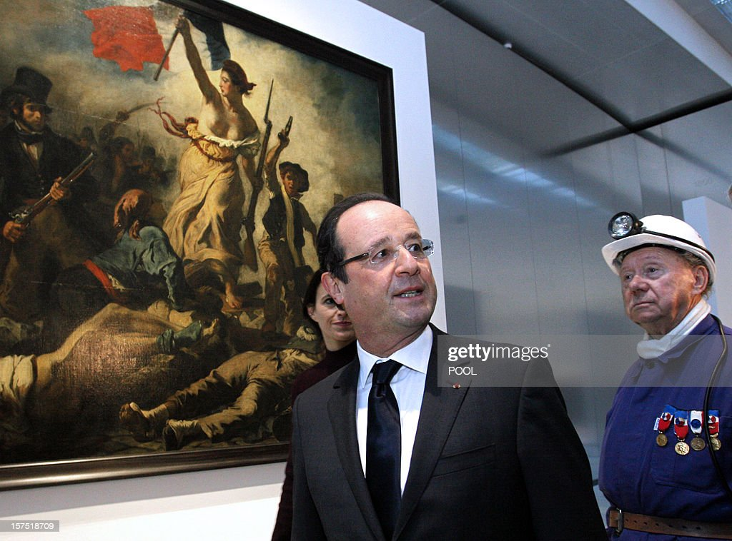 French President Francois Hollande (L) stands on December 4, 2012 with a former miner, Lucien Laurent, in front of in front of 'La Liberte Guidant le Peuple' ('Liberty Guiding the People'), a painting by Eugene Delacroix, during the inauguration of the Louvre-Lens Museum in the northern French town of Lens. The Paris museum opens on December 12 a gleaming new satellite in Lens. Blighted by the closure of the region's last mines 20 years ago, with unemployment at a stubbornly high 16 percent, Lens is hoping for a renaissance of its own from the glass and polished-aluminium structure.