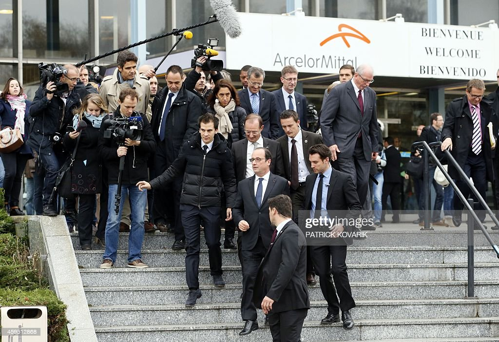 French President Francois Hollande surrounded by journalists leave after a visit to steel giant ArcelorMittal's office in Florange eastern France on...