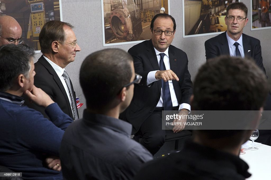 French President Francois Hollande talks during a meeting with ArcelorMittal workers during a visit to the ArcelorMittal Steel Factory in Florange...