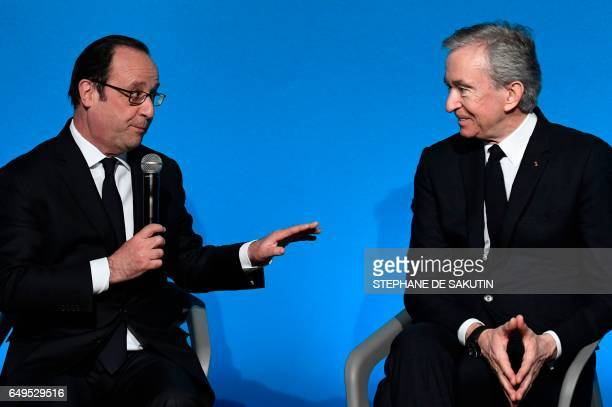 French president Francois Hollande talks to CEO of LVMH Bernard Arnault during a press conference to unveil a new museum in Paris on March 8 2017 The...