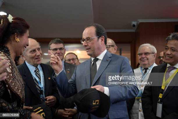 French President Francois Hollande talks to officials during a visit to a command room of the general direction of the marine surveillance in Jakarta...