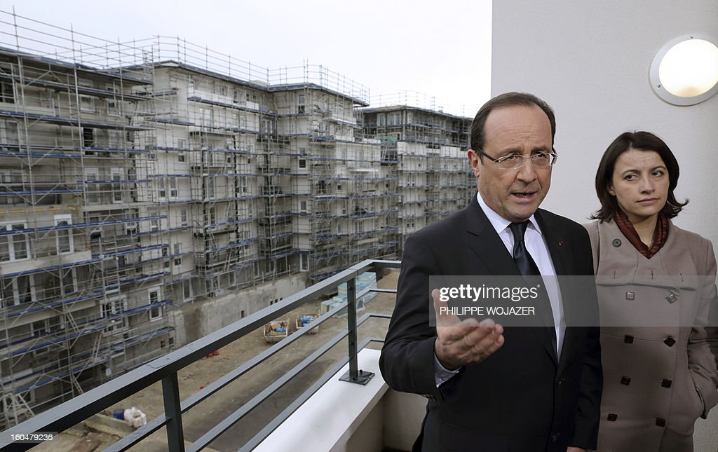 French President Francois Hollande talks to journalists next to Housing and Equality of Territories minister Cecile Duflot as they visit housing constructions at an urban redevelopment site in Ermont-Eaubonne near Paris on February 1, 2013. POOL