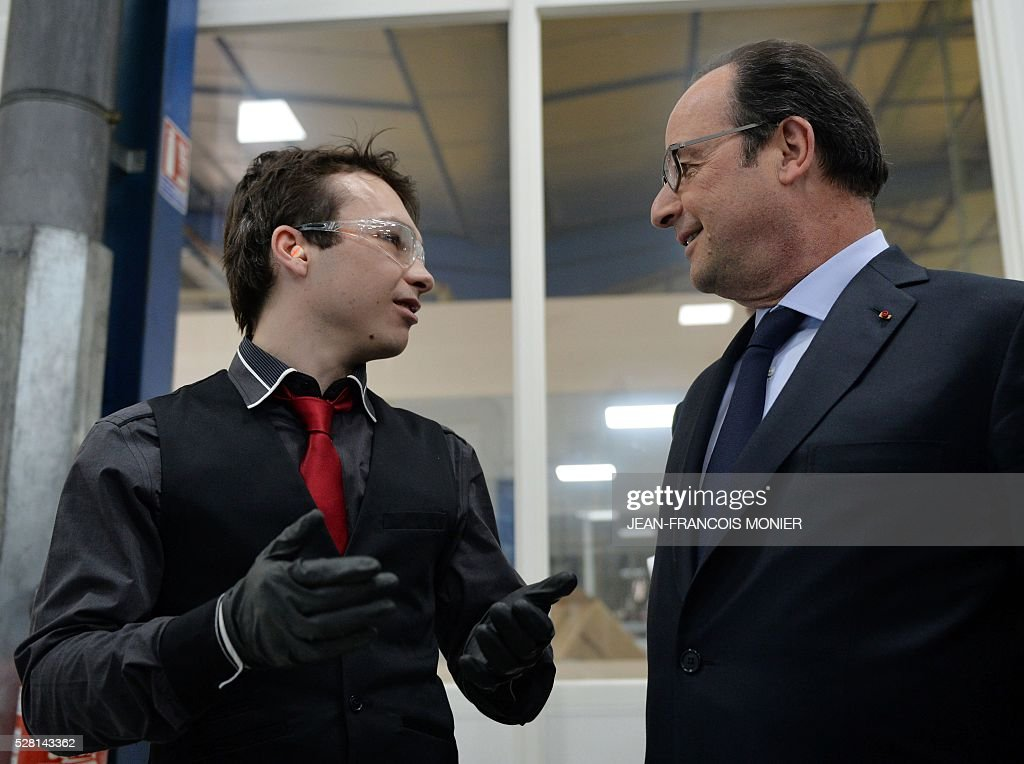 French President Francois Hollande (R) talks with a worker as he visits at the MK Automotive Mecachrome plant, on May 4, 2016 in Sable-sur-Sarthe, northwestern France. / AFP / JEAN