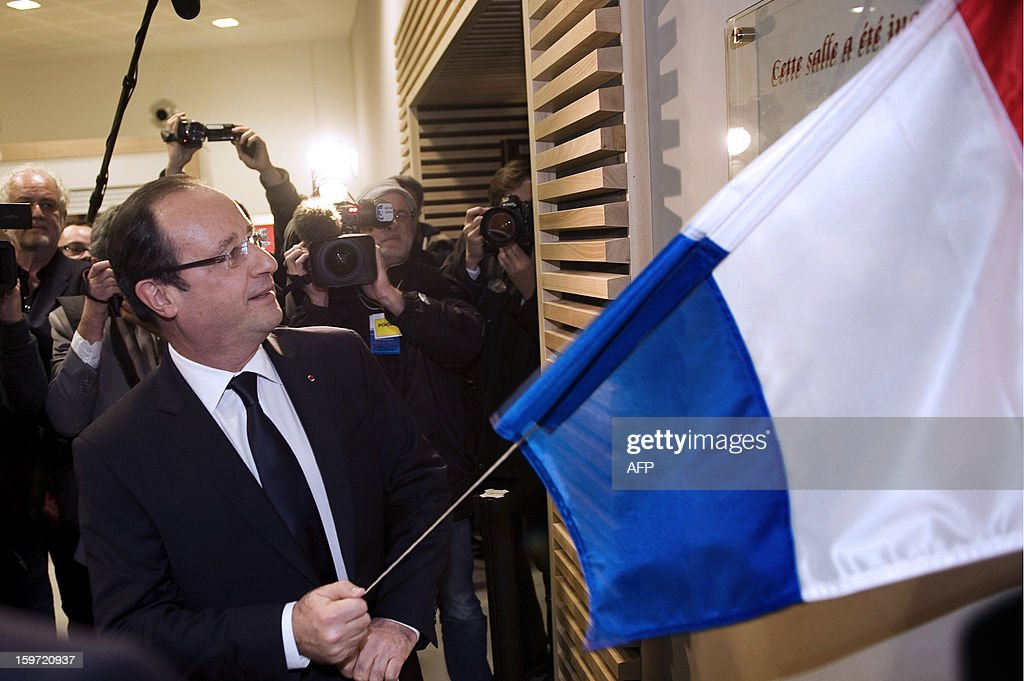 French President Francois Hollande unveils a plaque during the inauguration of a community hall in Auzelou a Tulle, Correze region central France on January 19, 2013.