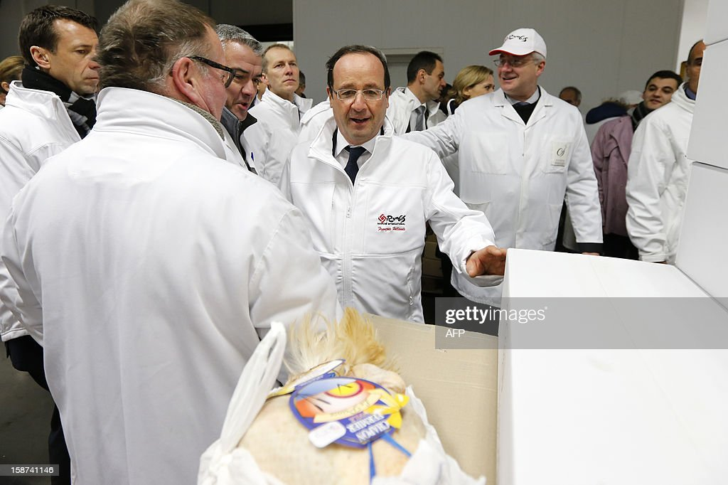 French President Francois Hollande (C) visits the poultry pavilion at the Rungis wholesale market in Rungis, near Paris on December 27, 2012. AFP PHOTO POOL / BENOIT TESSIER