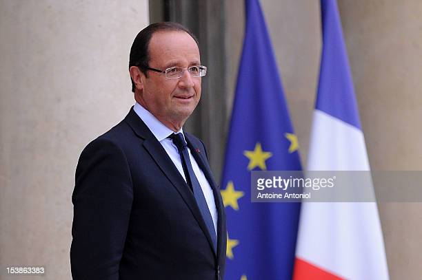 French President Francois Hollande waits for the arrival of U2 Frontman Bono and Microsoft Corp Chairman Bill Gates at the Elysee Palace on October...