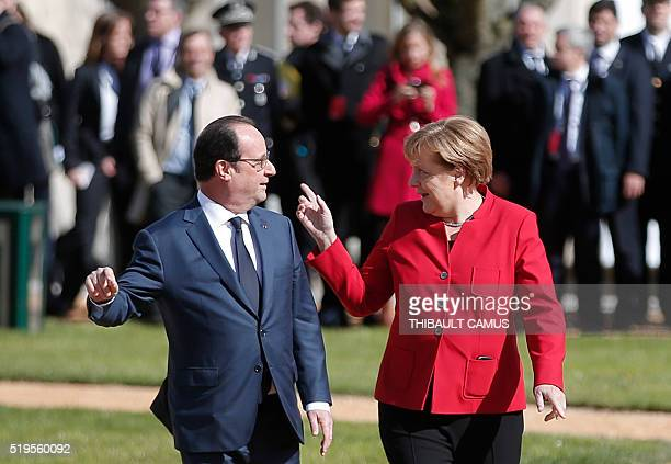 French President Francois Hollande walks next to German Chancellor Angela Merkel during a welcoming ceremony prior to the 18th FrancoGerman cabinet...