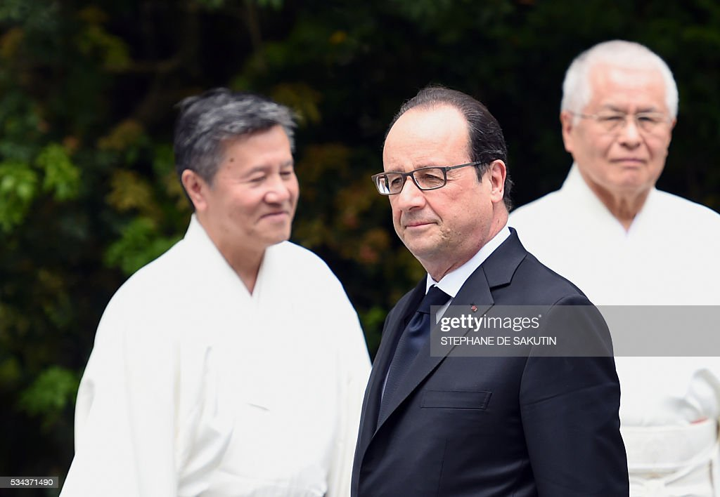 French President Francois Hollande (C) walks past Shinto priests as he arrives at Ise-Jingu Shrine in the city of Ise in Mie prefecture, on May 26, 2016 on the first day of the G7 leaders summit. World leaders kick off two days of G7 talks in Japan on May 26 with the creaky global economy, terrorism, refugees, China's controversial maritime claims, and a possible Brexit headlining their packed agenda. / AFP / STEPHANE