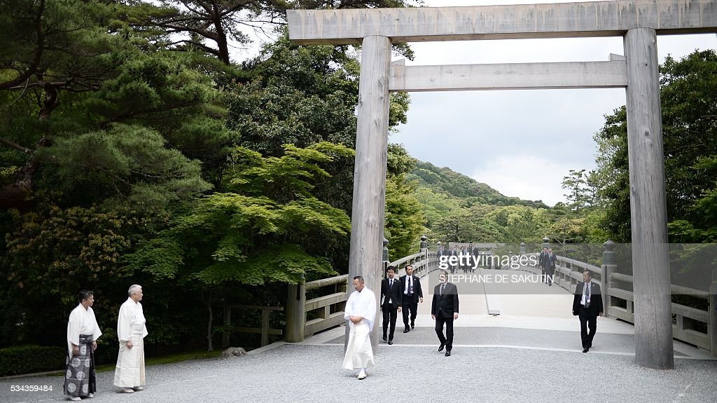 French President Francois Hollande (C) walks under a 'torii' or gate, as he arrives at Ise-Jingu Shrine in the city of Ise in Mie prefecture, on May 26, 2016, on the first day of the G7 leaders summit. World leaders kick off two days of G7 talks in Japan on May 26 with the creaky global economy, terrorism, refugees, China's controversial maritime claims, and a possible Brexit headlining their packed agenda. / AFP / STEPHANE