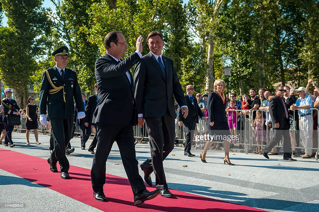 French President Francois Hollande (L) waves to the crowd as is welcomed by Slovenian President Borut Pahor (R) prior to their meeting on July 25, 2013, in Ljubljana. The presidents of eight western Balkans countries along with French president Francois Hollande met in Slovenia at an unprecedented summit aimed at promoting cooperation and further EU enlargement in the region. The summit was organized by the presidents of the only two former Yugoslav states that joined the EU, Slovenia's Borut Pahor and Croatia's Ivo Josipovic, and backed by the French president underlining the need for reforms for all Balkans states that would like to join the EU. AFP PHOTO / JURE MAKOVEC