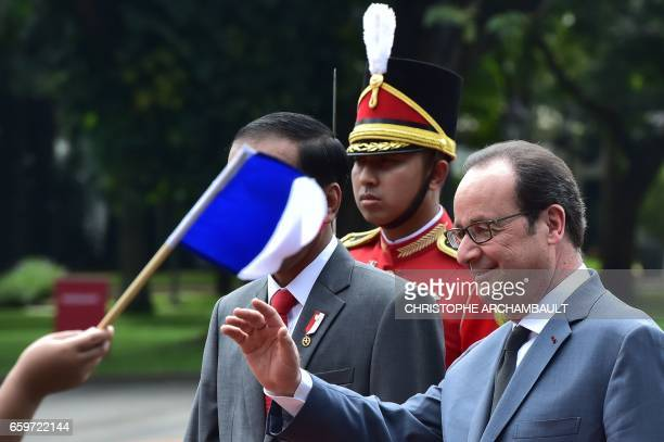 French President Francois Hollande waves to wellwishers as he walks with Indonesia's President Joko Widodo during his visit to the presidential...