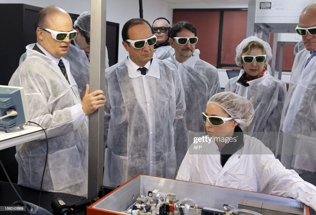 French President Francois Hollande (C) wearing security glasses looks at a technician at work as he visits the Amplitude Systemes plant, specialized in ultrafast diode-pumped solid-state lasers, in Pessac near Bordeaux, in southwestern France, on January 10, 2013.